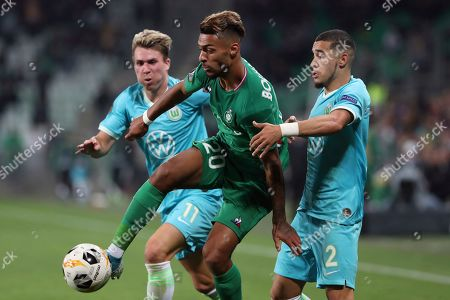 Saint-Etienne's Denis Bouanga, center, challenges for the ball with Wolfsburg's Felix Klaus, left, and William, right, during the Europa League group I soccer match between Saint-Etienne and VfL Wolfsburg at the Geoffroy Guichard stadium, in Saint-Etienne, central France
