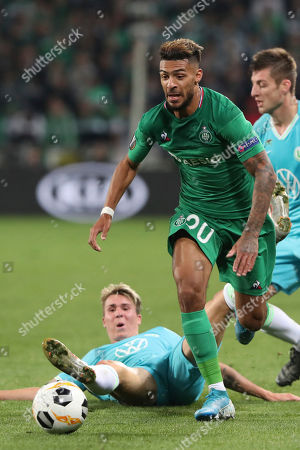 Saint-Etienne's Denis Bouanga, center, challenges for the ball with Wolfsburg's Felix Klaus, laying down on the field, during the Europa League group I soccer match between Saint-Etienne and VfL Wolfsburg at the Geoffroy Guichard stadium, in Saint-Etienne, central France