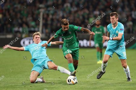 Saint-Etienne's Denis Bouanga, center, challenges for the ball with Wolfsburg's Felix Klaus, left, and Wolfsburg's Robin Knoche, right, during the Europa League group I soccer match between Saint-Etienne and VfL Wolfsburg at the Geoffroy Guichard stadium, in Saint-Etienne, central France