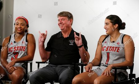 Kai Crutchfield, Wes Moore, Aislinn Konig. North Carolina State women's basketball coach Wes Moore, center, flashes the Wolfpack symbol as Kai Crutchfield, left, and Aislinn Konig look on during the Atlantic Coast Conference women's NCAA college basketball media day in Charlotte, N.C