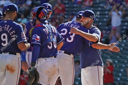 Texas Rangers starting pitcher Mike Minor (23) gets a hug from manager Chris Woodward, right, as he is removed from the game in the ninth inning against the Boston Red Sox during a baseball game, in Arlington, Texas