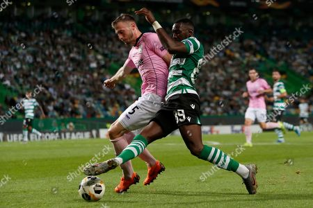 LASK's Petar Filipovic, left, vies for the ball with Sporting's Yannick Bolasie during the Europa League group D soccer match between Sporting CP and LASK at the Alvalade stadium in Lisbon