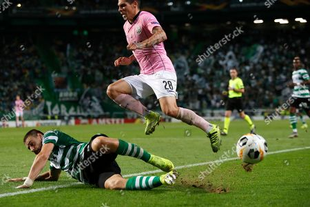Sporting's Sebastian Coates, left, tackles LASK's Dominik Frieser during the Europa League group D soccer match between Sporting CP and LASK at the Alvalade stadium in Lisbon