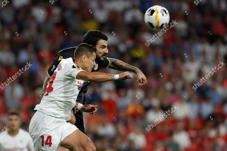 APOEL's Giorgos Merkis, top, jumps for a header with Sevilla's Javier Hernandez during the Europa League group A soccer match between Sevilla and APOEL Nicosia at the Estadio Ramon Sanchez-Pizjuan stadium in Seville, Spain