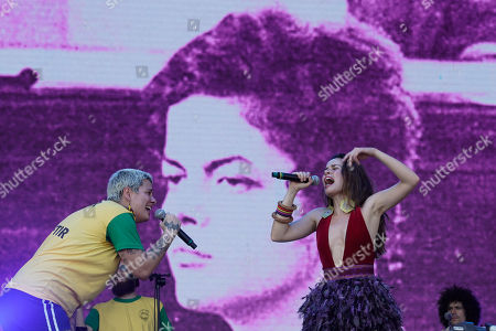 A picture of former Brazilian President Dilma Rousseff, taken during the dictatorship years in Brazil, is displayed on the big screen as Juliana Strassacapa of the Brazilian band Francisco, el Hombre and Catalina Garcia, of the Colombian band Monsieur Perine, right, perform at the Rock in Rio music festival in Rio de Janeiro, Brazil