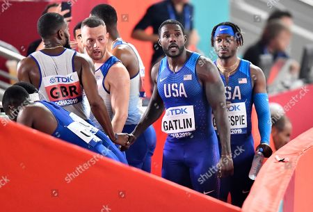 The United States relay team with Justin Gatlin, center, and Cravon Gillespie, right, leave after the men's 4x100 meter relay at the World Athletics Championships in Doha, Qatar