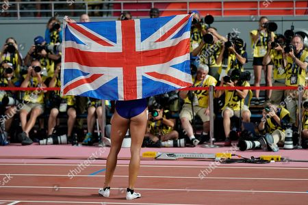 Katarina Johnson-Thompson, of Great Britain, poses with her country's flag for photographers after winning the heptathlon at the World Athletics Championships in Doha, Qatar