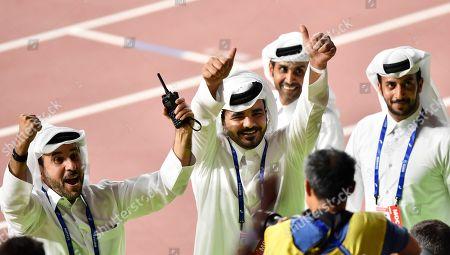 Sheikh Joaan bin Hamad bin Khalifa Al Thani, center, of Qatar, flashes two thumbs up when celebrating Mutaz Essa Barshim's gold medal in the men's high jump at the World Athletics Championships in Doha, Qatar