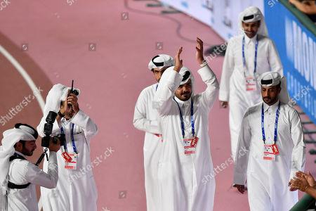 Sheikh Joaan bin Hamad bin Khalifa Al Thani, center, of Qatar, applauds when celebrating Mutaz Essa Barshim's gold medal in the men's high jump at the World Athletics Championships in Doha, Qatar