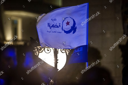 A supporter of Islamist party Ennahda holds a party flag during a meeting with President of the Islamist party Ennahda and candidate for the upcoming Parliamentary election Rached Ghannouchi in Tunis, Tunisia, . The parliamentary election are set for Sunday Oct.6, 2019