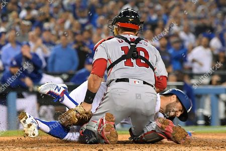 Los Angeles Dodgers' Chris Taylor, rear, is tagged out at home by Washington Nationals catcher Yan Gomes while trying to score during the fifth inning of Game 1 in baseball's National League Divisional Series, in Los Angeles