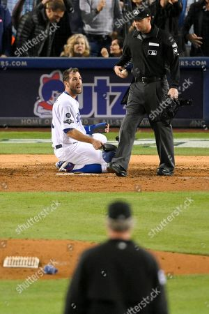 Los Angeles Dodgers' Chris Taylor, reacts after being tagged out at home by Washington Nationals catcher Yan Gomes during the fifth inning of Game 1 in baseball's National League Divisional Series, in Los Angeles