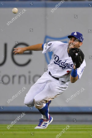 Los Angeles Dodgers left fielder Chris Taylor catches a line drive by Washington Nationals' Howie Kendrick during the seventh inning of Game 1 in baseball's National League Divisional Series, in Los Angeles