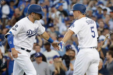 Los Angeles Dodgers' A.J. Pollock, left, celebrates with Corey Seager after scoring on a bases-loaded walk during the first inning of Game 1 in baseball's National League Divisional Series against the Washington Nationals, in Los Angeles