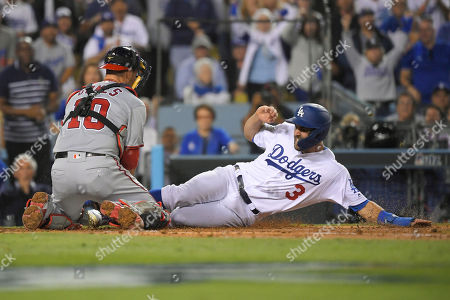Los Angeles Dodgers' Chris Taylor, right, is tagged out at home by Washington Nationals catcher Yan Gomes while trying to score during the fifth inning of Game 1 in baseball's National League Divisional Series, in Los Angeles