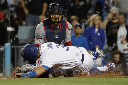 Los Angeles Dodgers' Chris Taylor, front, is tagged out at home by Washington Nationals catcher Yan Gomes while trying to score during the fifth inning of Game 1 in baseball's National League Divisional Series, in Los Angeles