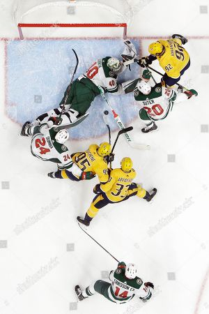 Minnesota Wild goaltender Devan Dubnyk (40) lies on the ice as he blocks the puck during a scramble in front of the net in the first period of the team's NHL hockey game against the Nashville Predators, in Nashville, Tenn