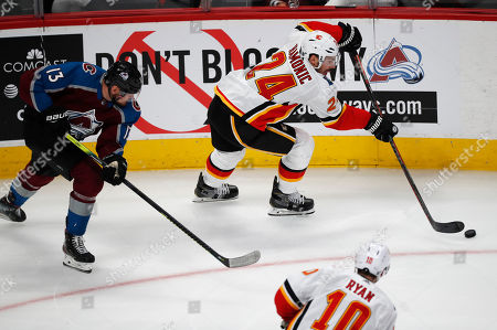 Colorado Avalanche right wing Valeri Nichushkin, left, pursues as Calgary Flames defenseman Travis Hamonic, top right, picks up a loose puck to pass to center Derek Ryan during the third period of an NHL hockey game, in Denver. Colorado won 5-3