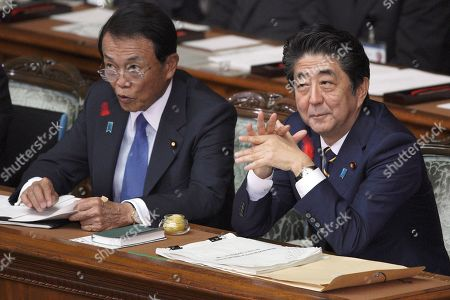Japanese Prime Minister Shinzo Abe, right, pauses next to Finance Minister Taro Aso before delivering a policy speech during the opening of an extraordinary parliament session in Tokyo