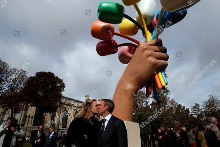 "New York-based artist Jeff Koons poses with his wife Justine Wheeler as he unveiled his much-awaited and controversial sculpture ""Bouquet of Tulips"" dedicated to the victims of the terrorists attacks, in a garden next to the Champs Elysee near the Petit Palais museum in Paris"
