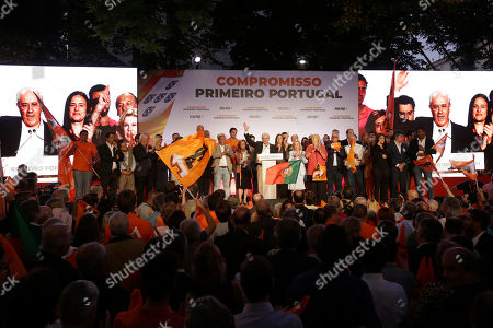 """Rui Rio, leader of the Social Democratic Party, center, gestures during an election campaign rally in Lisbon . Portugal will hold a general election on Oct. 6 in which voters will choose members of the next Portuguese parliament. Slogan in the background reads, """"Commitment, Portugal First"""