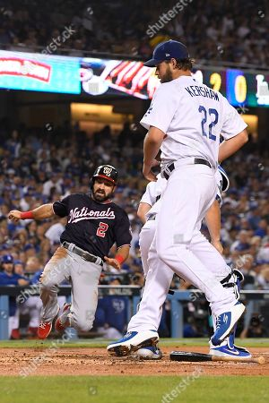 Washington Nationals' Adam Eaton, left, scores past Los Angeles Dodgers starting pitcher Clayton Kershaw on a double by Anthony Rendon during the second inning in Game 2 of a baseball National League Division Series, in Los Angeles