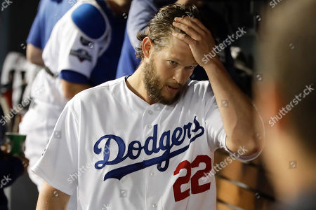 Los Angeles Dodgers starting pitcher Clayton Kershaw walks in the dugout after leaving the during the sixth inning in Game 2 of the baseball team's National League Division Series against the Washington Nationals, in Los Angeles