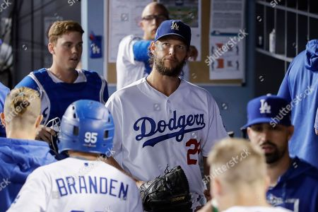 Los Angeles Dodgers starting pitcher Clayton Kershaw walks in the dugout after leavingduring the sixth inning in Game 2 of the baseball team's National League Division Series against the Washington Nationals, in Los Angeles