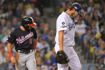 Washington Nationals' Adam Eaton, left, scores past Los Angeles Dodgers starting pitcher Clayton Kershaw on a double by Anthony Rendon during the second inning in Game 2 of baseball's National League Division Series against the Los Angeles Dodgers, in Los Angeles