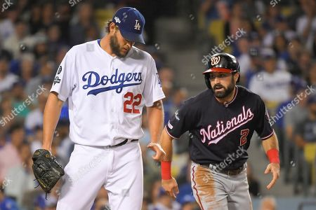 Washington Nationals' Adam Eaton, right, scores past Los Angeles Dodgers starting pitcher Clayton Kershaw on a double by Anthony Rendon during the second inning in Game 2 of a baseball National League Division Series, in Los Angeles