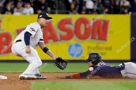 Minnesota Twins' Jorge Polanco (11) steals second base ahead of the throw to New York Yankees second baseman Gleyber Torres during the fifth inning of Game 1 of an American League Division Series baseball game, in New York