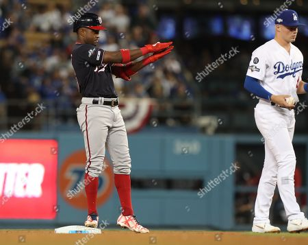 Washington Nationals center fielder Victor Robles (L) reacts after hitting a double off Los Angeles Dodgers starting pitcher Clayton Kershaw as Los Angeles Dodgers shortstop Gavin Lux (R) looks on in the top of the sixth inning of the MLB National League Division Series playoff baseball game two between the Washington Nationals and the Los Angeles Dodgers at Dodgers Stadium in Los Angeles, California, USA, 04 October 2019.