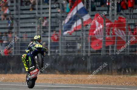 Italy's rider Valentino Rossi of the Movistar Energy Yamaha MotoGP Team lifts the front wheel of his bike after completing the qualifying round of Thailand's MotoGP at the Chang International Circuit in Buriram, Thailand
