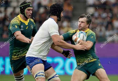 Australia's Adam Ashley-Cooper, right, is tackled by Uruguay's Manuel Leindekar during the Rugby World Cup Pool D game at Oita Stadium between Australia and Uruguay in Oita, Japan