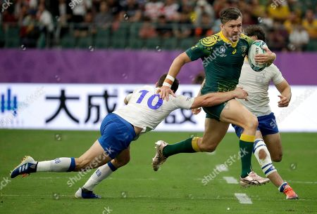 Stock Picture of Australia's Adam Ashley-Cooper attempts to break the tackle of Uruguay's Felipe Berchesi during the Rugby World Cup Pool D game at Oita Stadium between Australia and Uruguay in Oita, Japan