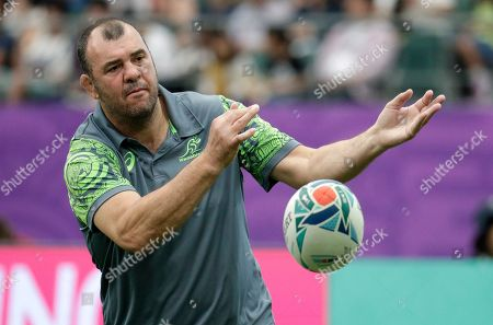 Australian coach Michael Cheika passes the ball as his team warms up ahead of the Rugby World Cup Pool D game at Oita Stadium between Australia and Uruguay in Oita, Japan