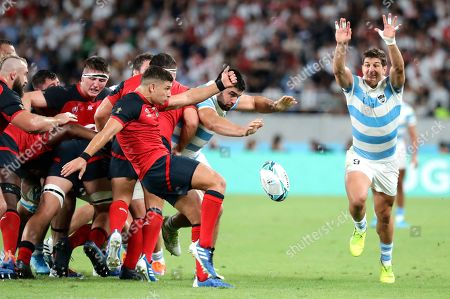 England's Ben Youngs, left, kicks the ball as Argentina's Tomas Cubelli attempts to charge it down during the Rugby World Cup Pool C game at Tokyo Stadium between England and Argentina in Tokyo, Japan
