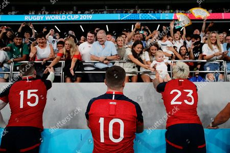England's Jack Nowell (23) hands off the baby to his wife as he celebrates with teammates after the Rugby World Cup Pool C game at Tokyo Stadium against Argentina in Tokyo, Japan, . England won 39-10