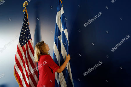 A woman adjusts a Greek and a USA flag prior the speech of the US State Secretary Mike Pompeo (not pictured), at the Stavros Niarchos Foundation Cultural Centre (SNFCC), in Athens, Greece, 05 October 2019. Pompeo is on a two-days official visit to Greece.