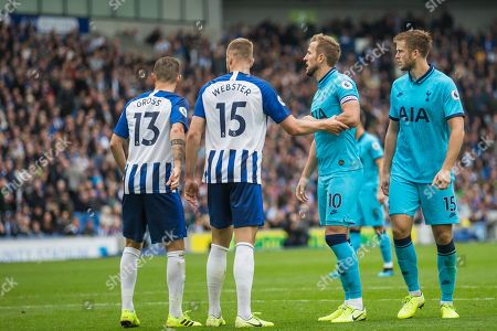 Pascal Gross (Brighton) with Adam Webster (Brighton) holding the arm of Harry Kane (Tottenham) with Eric Dier (Tottenham) alongside during the Premier League match between Brighton and Hove Albion and Tottenham Hotspur at the American Express Community Stadium, Brighton and Hove