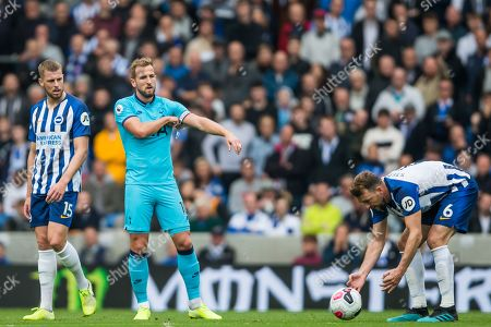 Dale Stephens (Brighton) placing the ball while Harry Kane (Tottenham) adjusts his 'Captain' armband looked on by Adam Webster (Brighton) during the Premier League match between Brighton and Hove Albion and Tottenham Hotspur at the American Express Community Stadium, Brighton and Hove
