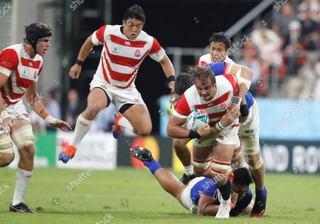 Japan's James Moore, right, is tackled by a Samoan defender during the Rugby World Cup Pool A game at City of Toyota Stadium between Japan and Samoa in Tokyo City, Japan