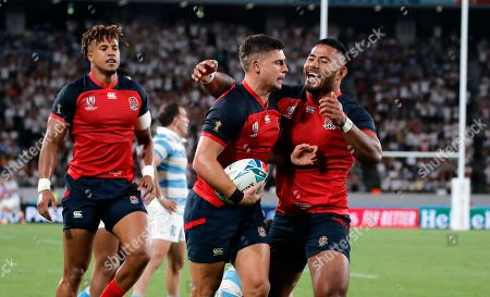England's Ben Youngs, center, celebrates with teammate Manu Tuilagi after scoring a try against Argentina during the Rugby World Cup Pool C game at Tokyo Stadium in Tokyo, Japan