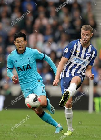 Brighton's Adam Webster, tight, challenges for the ball with Tottenham's Son Heung-min during the English Premier League soccer match between Brighton and Hove Albion and Tottenham Hotspur at Falmer stadium in Brighton, England