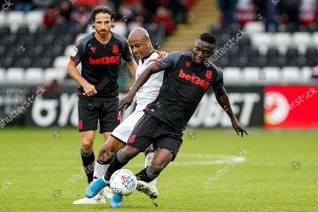 Oghenekaro Etebo of Stoke City and Andre Ayew of Swansea City