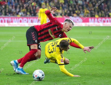 Freiburg's Robin Koch (L) in action against Dortmund's Thorgan Hazard during the German Bundesliga soccer match between SC Freiburg and Borussia Dortmund in Freiburg, Germany, 05 October 2019.