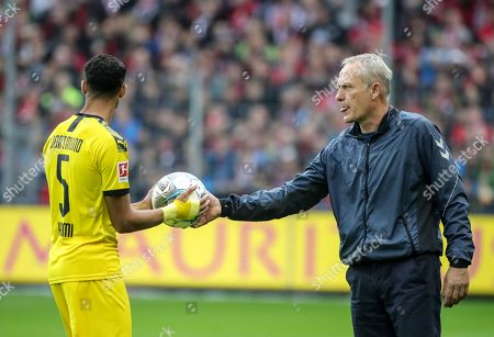 Freiburg's head coach Christian Streich (R) gives the ball to Dortmund's Achraf Hakimi during the German Bundesliga soccer match between SC Freiburg and Borussia Dortmund in Freiburg, Germany, 05 October 2019.