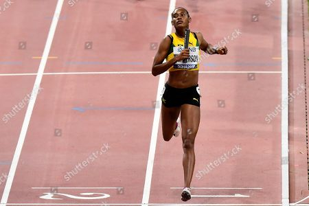 Stephenie Ann McPherson of Jamaica crosses the finish line to win her heat of the women's 4x400 meter relay during the World Athletics Championships in Doha, Qatar