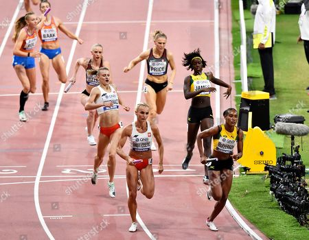 Stephenie Ann McPherson of Jamaica, right, and Justyna Swiety-Ersetic of Poland lead their heat of the women's 4x400 meter relay during the World Athletics Championships in Doha, Qatar