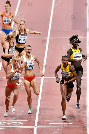 Stock Picture of Stephenie Ann McPherson of Jamaica, foreground right, and Justyna Swiety-Ersetic of Poland, foreground left, lead their heat of the women's 4x400 meter relay during the World Athletics Championships in Doha, Qatar